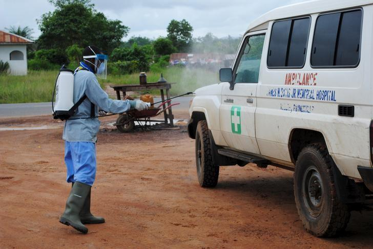 A health worker sprays disinfectant on an ambulance in Nedowein, Liberia, July 15, 2015. REUTERS/James Giahyue/Files
