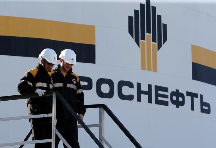 Workers stand next to a logo of Russia's Rosneft oil company at the central processing facility of the Rosneft-owned Priobskoye oil field outside the West Siberian city of Nefteyugansk, Russia, August 4, 2016. REUTERS/Sergei Karpukhin/Files