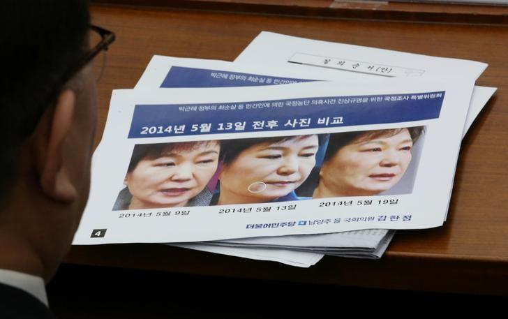Kim Young-jae, who heads a hospital regularly visited by impeached President Park Geun-hye's longtime friend Choi Soon-sil, looks at impeached President Park Geun-hye's three pictures combo each taken on May 9th, May 13th, May 19, 2014 respectivelly. The letters read ''The photos are comparing Park's face around May 13th''.  REUTERS/Ahn Young-joon/Pool