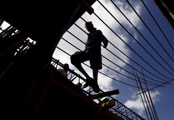 A labourer walks on an iron frame at the construction site of a residential complex on the outskirts of Kolkata, India, November 2, 2015. REUTERS/Rupak De Chowdhuri/File Photo