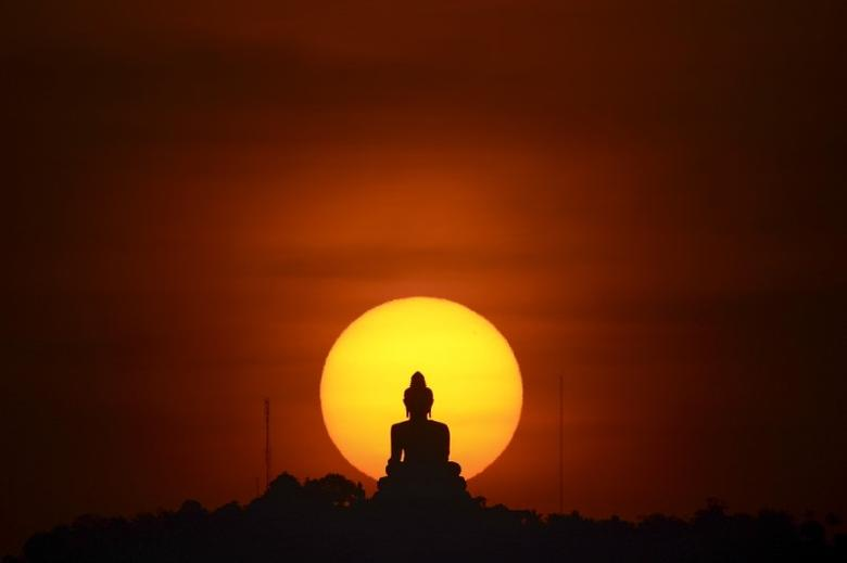A sun sets behind a buddha statue in Phuket, Thailand March 18, 2016. REUTERS/Athit Perawongmetha/Files