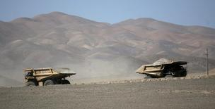 Camiones atraviesan el desierto cerca de la minera La Escondida, en los alrededores de Antofagasta, 31 de marzo 2008. La utilidad de la chilena Escondida, la mina de cobre más grande del mundo, cayó un 43 por ciento entre enero y septiembre presionada por una baja en su producción, menores leyes del mineral y débiles precios del metal, pese a un retroceso en sus costos.REUTERS/Ivan Alvarado (CHILE) - RTR1Z84O
