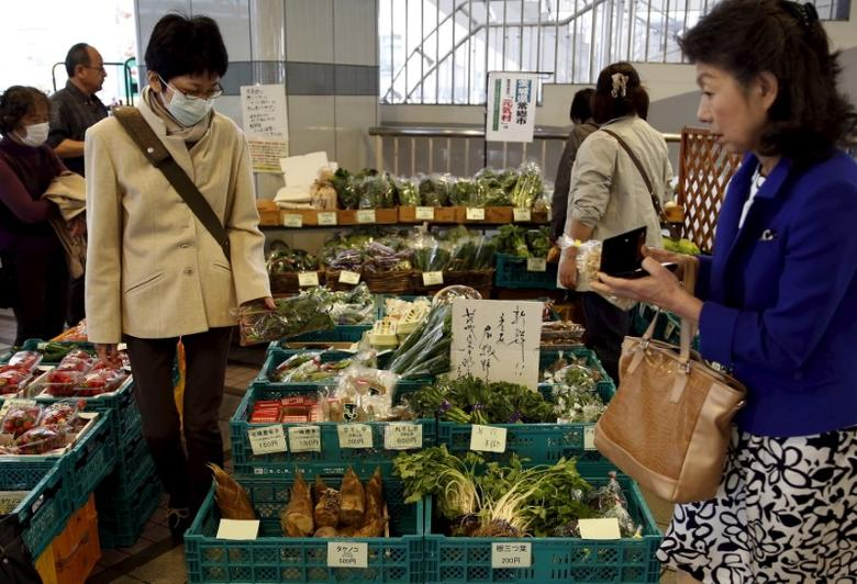 Shoppers look at vegetables at a greengrocer at Ginza shopping district in Tokyo, Japan, March 31, 2016. REUTERS/Yuya Shino