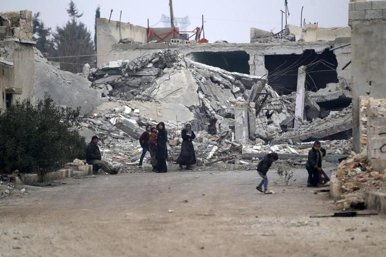 People stand near near rubble of damaged buildings in al-Rai town, northern Aleppo countryside, Syria December 25, 2016. REUTERS/Khalil Ashawi