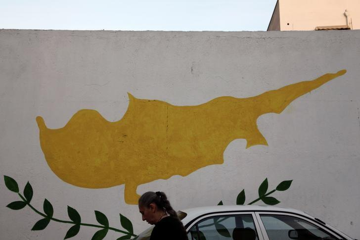 A woman walks in front of Cypriot flag painted on a wall in capital Nicosia, Cyprus November 11, 2016. REUTERS/Yiannis Kourtoglou/Files