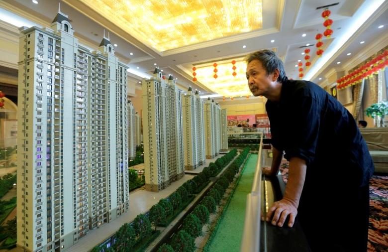 A visitor looks at a model of a new apartment complex at a showroom of Evergrande Real Estate Group in Wuhan, Hubei province, November 9, 2013.   REUTERS/Stringer/File Photo