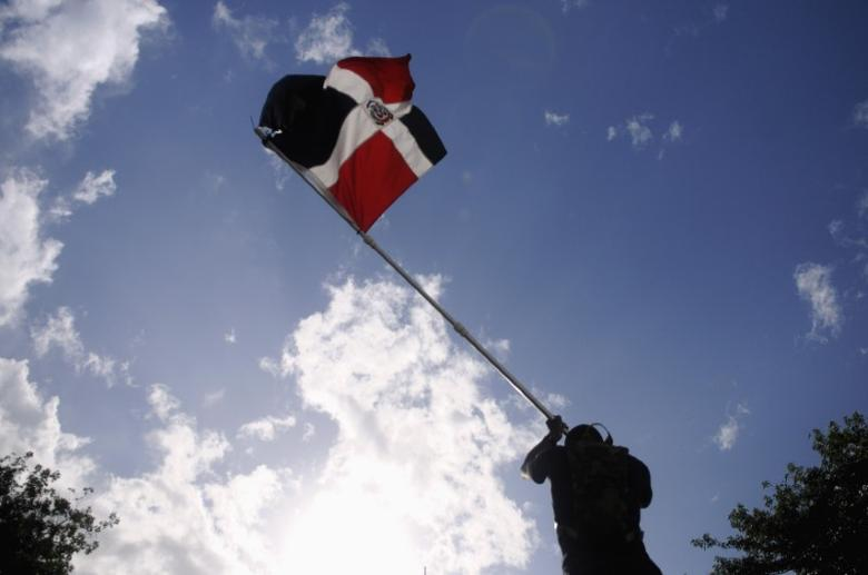 A protester waves a Dominican Republic flag as thousands of Dominicans protested against fiscal reform in the independence park, in Santo Domingo November 11, 2012. REUTERS/Ricardo Rojas