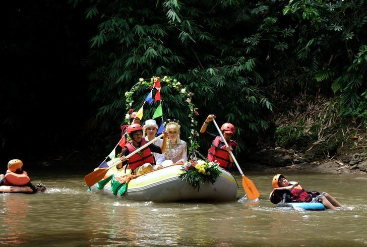 Novanto Rahman and his bride Sandra Fidelia Novianti, a volunteer who takes part in a Ciliwung river clean-up initiative, hold part of their wedding ceremony on the Ciliwung, which runs more than 100 km (60 miles) from its source in West Java to Jakarta bay, in Depok south of Jakarta, Indonesia December 18, 2016. Picture taken December 18, 2016. REUTERS/Adi Kurniawan
