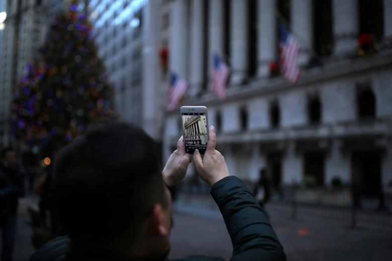 A tourist takes a photo outside the New York Stock Exchange (NYSE) in Manhattan, New York City, U.S., December 30, 2016. REUTERS/Stephen Yang