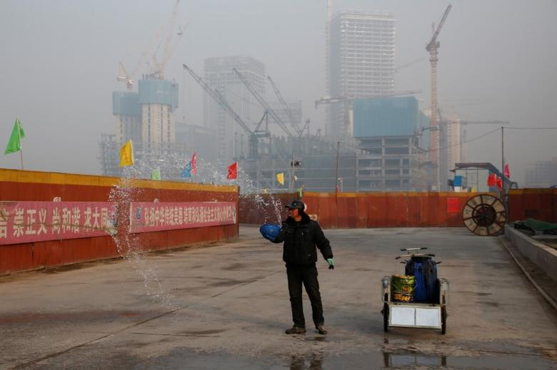 A worker sprinkles water onto a road at a construction site in Beijing, China, December 31, 2016.  REUTERS/Thomas Peter