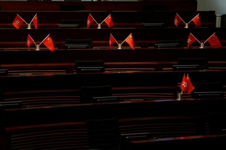 Empty seats with China and Hong Kong flags are seen inside a chamber after pro-Beijing lawmakers staged a walk-out to stall legislator-elects Baggio Leung and Yau Wai-ching from swearing in at the Legislative Council in Hong Kong, China October 19, 2016. REUTERS/Bobby Yip/Files