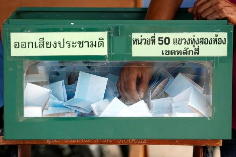 An election commission official holds a ballot paper from a ballot box while counting votes during a constitutional referendum vote at a polling station in Bangkok, Thailand, August 7, 2016.  REUTERS/Chaiwat Subprasom/Files