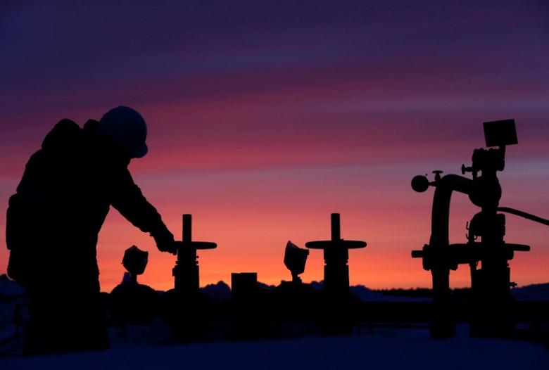 A worker checks the valve of an oil pipe at an oil field owned by Russian state-owned oil producer Bashneft near the village of Nikolo-Berezovka, northwest of Ufa, Bashkortostan, Russia January 28, 2015. REUTERS/Sergei Karpukhin/File Photo