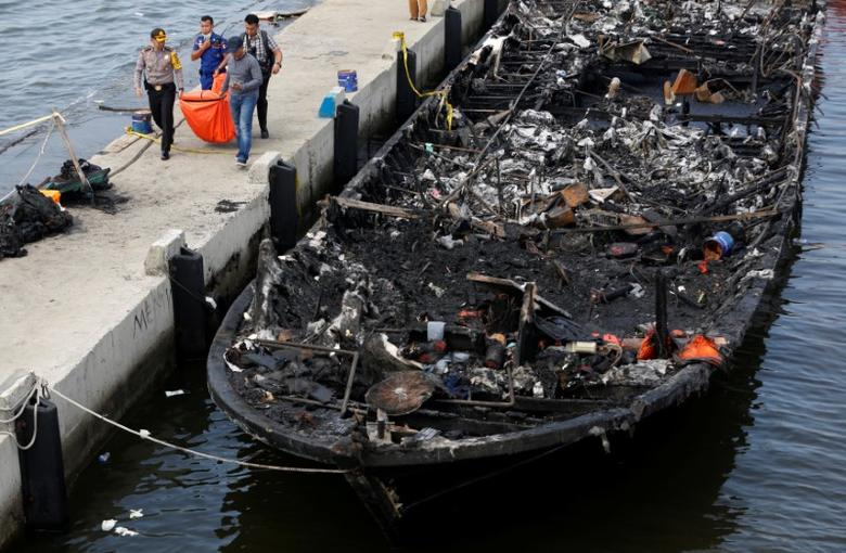The remains of a victim is carried away after a fire ripped through a boat carrying tourists to islands north of the capital, at Muara Angke port in Jakarta, Indonesia January 1, 2017. REUTERS/Darren Whiteside