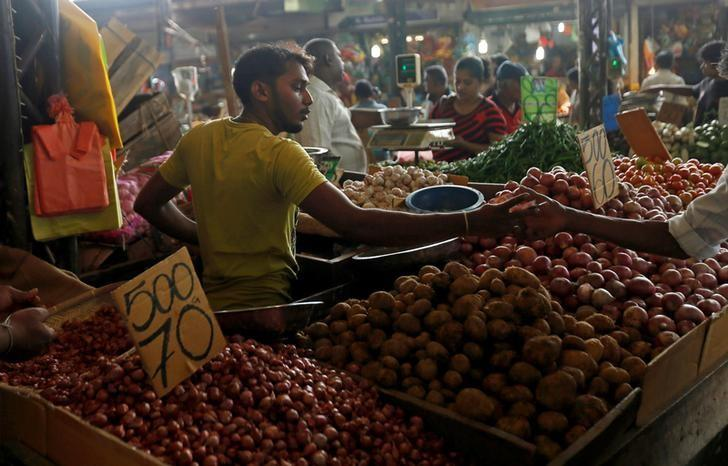 A vendor of a stall exchanges money with a customer at a main market in Colombo, Sri Lanka November 30, 2016. REUTERS/Dinuka Liyanawatte