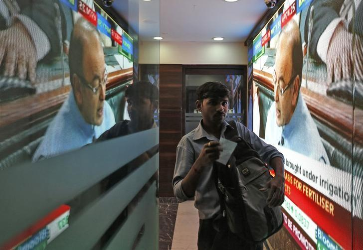 A man walks in a lobby as a telecast of India's Finance Minister Arun Jaitley presenting the budget is displayed inside the Bombay Stock Exchange (BSE) building in Mumbai, India, February 29, 2016. REUTERS/Danish Siddiqui/Files