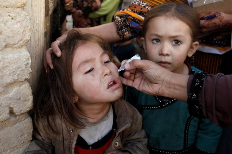 A girl receives polio vaccine drops from an anti-polio vaccination worker outside her family home in Quetta, Pakistan January 2, 2017. REUTERS/ Naseer Ahmed