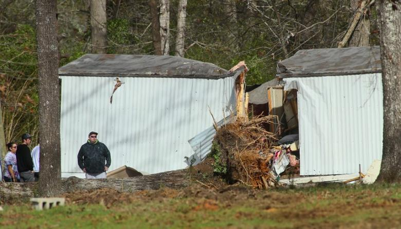 Friends and family survey the trailer where a tree fell and killed four people after a deadly storm hit Rehobeth, Alabama, U.S. January 3, 2017. REUTERS/Phil Sears
