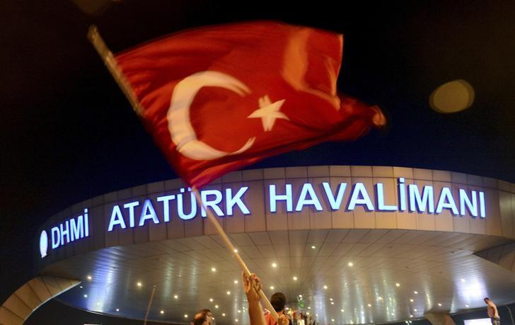 A man waves a Turkish flag in front of Ataturk Airport during an attempted coup in Istanbul, Turkey July 16, 2016. REUTERS/IHLAS News Agency/Files