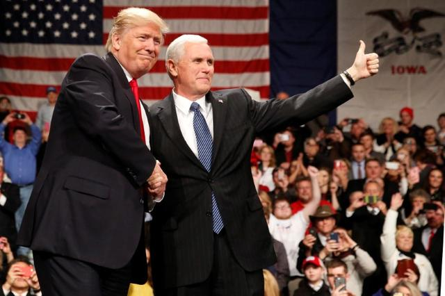 U.S. President-elect Donald Trump shakes hands with Vice President-elect Mike Pence (R) at the USA Thank You Tour event at the Iowa Events Center in Des Moines, Iowa, U.S., December 8, 2016. REUTERS/Shannon Stapleton