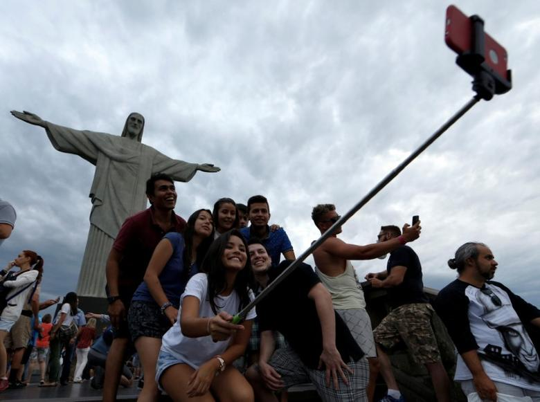 Tourists pose for a selfie before a ceremony with the Paralympic torch at the Christ the Redeemer statue ahead of the 2016 Rio Paralympic games in Rio de Janeiro, Brazil September 6, 2016. REUTERS/Carlos Garcia Rawlins