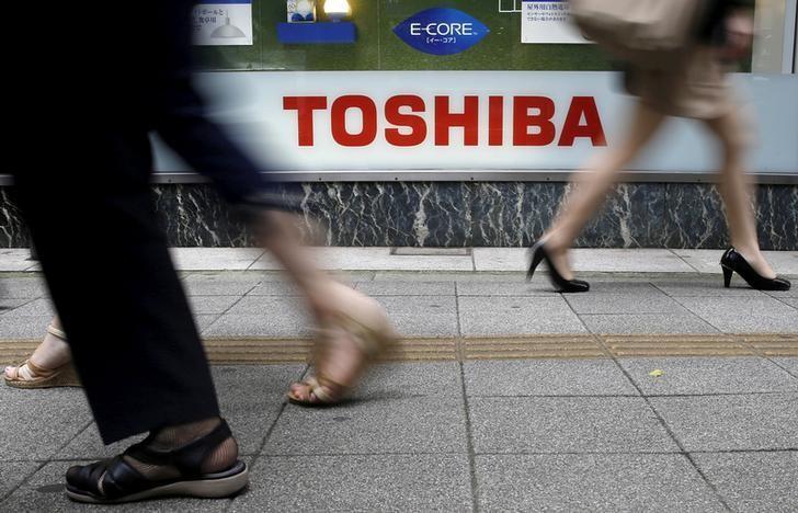 Pedestrians walk past a logo of Toshiba Corp outside an electronics retailer in Tokyo, Japan September 14, 2015.   REUTERS/Toru Hanai/File Photo