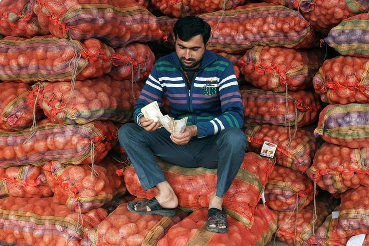 A vendor counts old 500 Indian rupee banknotes as he sits on sacks of potatoes at a wholesale vegetable market in Jammu, November 22, 2016. REUTERS/Mukesh Gupta/Files