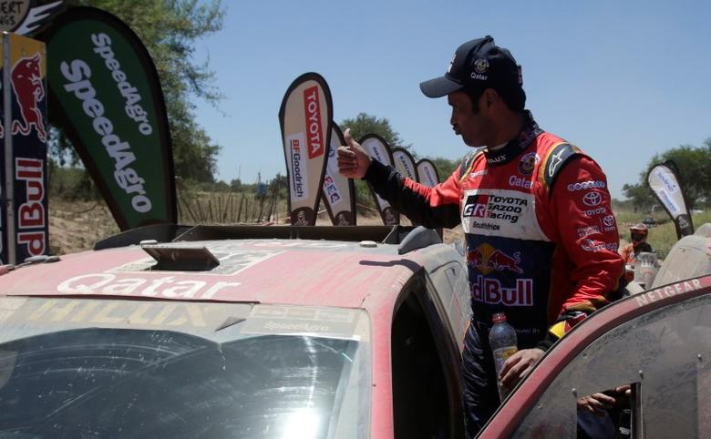 Nasser Al-Attiyah of Qatar gestures after driving his Toyota with his co-pilot Matthieu Baumel.  REUTERS/Ricardo Moraes