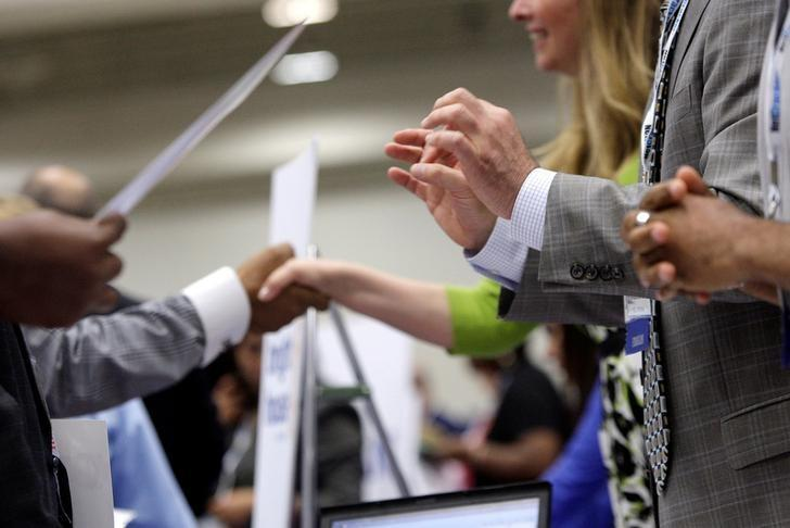Corporate recruiters (R) gesture and shake hands as they talk with job seekers at a Hire Our Heroes job fair targeting unemployed military veterans and sponsored by the Cable Show, a cable television industry trade show in Washington, June 11, 2013. REUTERS/Jonathan Ernst/File Photo