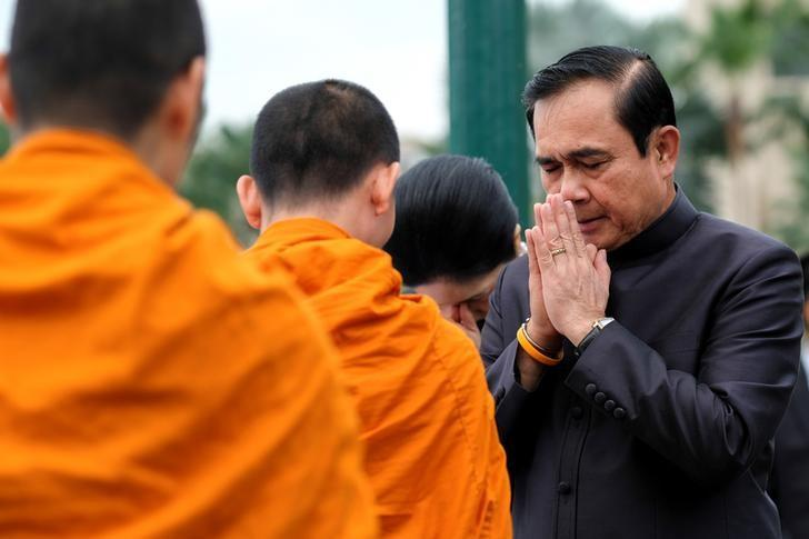 Thailand's Prime Minister Prayuth Chan-ocha (R) offers alms to buddhist monks before a weekly cabinet meeting at Government House in Bangkok, Thailand, January 4, 2017. REUTERS/Athit Perawongmetha