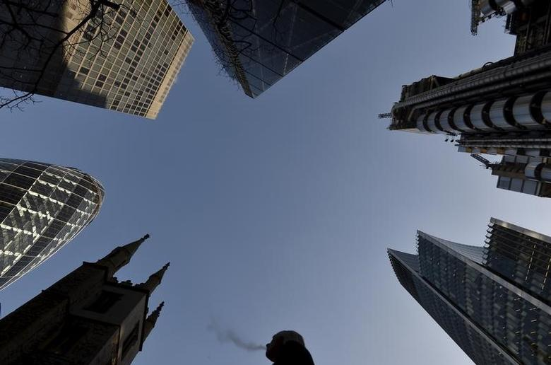 A city worker walks through the City of London with St. Andrew Undershaft church surrounded by business skyscrapers, December 16, 2014. REUTERS/Toby Melville