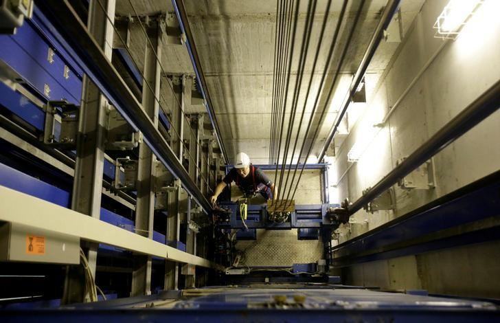 A service engineer of Germany's industrial conglomerate ThyssenKrupp AG looks after the mounting of an elevator inside an elevator shaft at an office building in Berlin, Germany September 17, 2013.  REUTERS/Tobias Schwarz/File photo