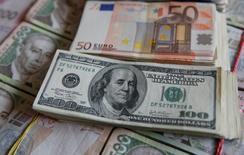 Le dollar américain va conserver sa vigueur par rapport à l'euro et a même de bonnes chances de parvenir à la parité face à la monnaie unique européenne cette année en raison des anticipations sur une hausse des taux d'intérêt aux Etats-Unis, montre une enquête Reuters publiée vendredi. /Photo prise le 31 octobre 2016/REUTERS/Valentyn Ogirenko