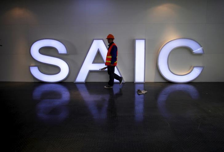 A worker walks past a lighted signage of the Shanghai Automotive Industry Corporation (SAIC) before the opening of the 15th Shanghai International Automobile Industry Exhibition in Shanghai in this April 19, 2013 file photo.  REUTERS/Carlos Barria/File Photo