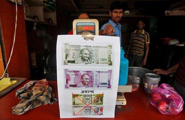 FILE PHOTO: A notice is pasted at a shop stating the refusal of the acceptance of the old 500 and 1000 Indian rupee banknotes and acceptance of the new 500 and 2000 Indian rupee banknotes, in Allahabad, India, November 10, 2016. REUTERS/Jitendra Prakash/File photo