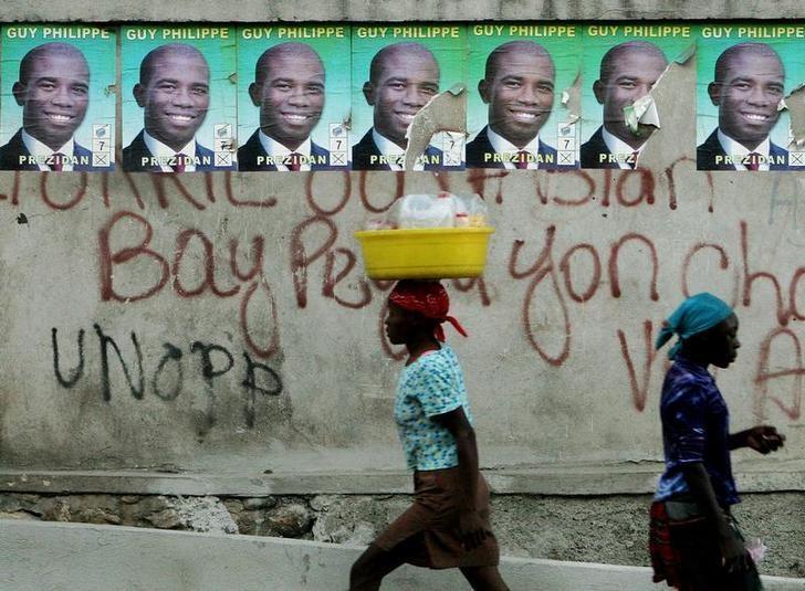 Haitians walk past posters of Guy Philippe at a street in Port-au-Prince, Haiti, February 3, 2006. REUTERS/Eduardo Munoz
