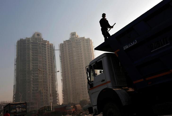 A labourer stands on a truck carrying construction materials at a construction site of residential buildings in Noida on the outskirts of New Delhi November 29, 2013.  REUTERS/Adnan Abidi/Files