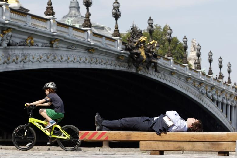 A man relaxes in the sun near the Alexandre III bridge along the Seine River as people take advantage of late summer weather in Paris August 26, 2013.   REUTERS/Charles Platiau