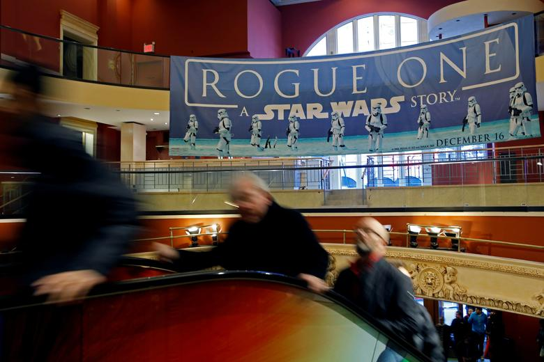 People ride an escalator under a Star Wars Rogue One poster at AMC Empire 25 on Christmas Day in Manhattan, New York City, U.S., December 25, 2016. REUTERS/Andrew Kelly - RTX2WFY1