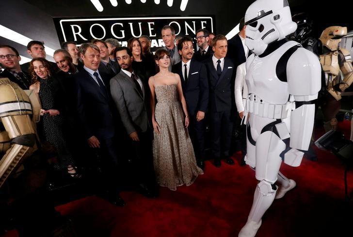 The cast and crew pose on the red carpet while a ''Storm Trooper'' walks by as they arrive at the world premiere of the film ''Rogue One: A Star Wars Story'' in Hollywood, California, U.S., December 10, 2016.  REUTERS/Mario Anzuoni/Files