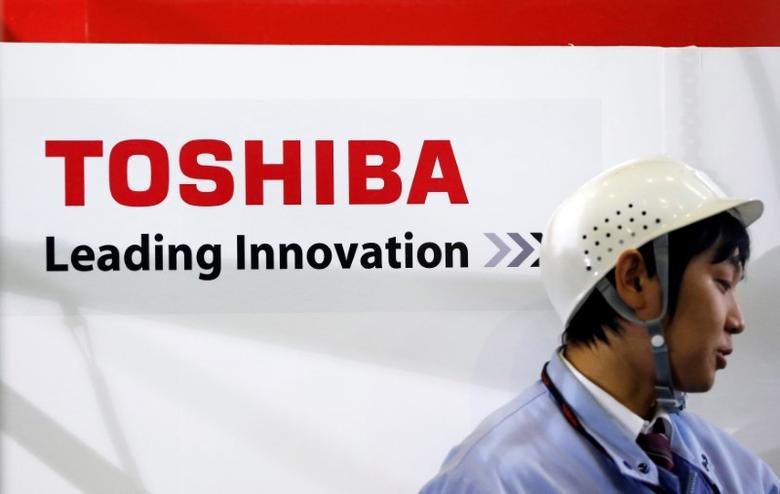An employee stands next to a logo of Toshiba Corp in Yokohama, south of Tokyo November 21, 2012.   REUTERS/Yuriko Nakao/File Photo
