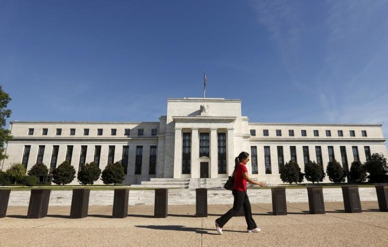 A woman walks past the Federal Reserve headquarters in Washington September 16, 2015. REUTERS/Kevin Lamarque