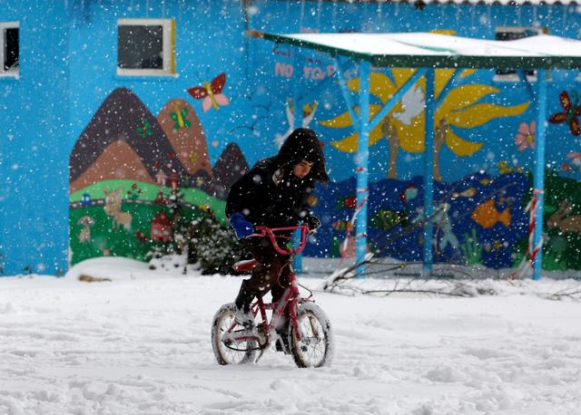 A stranded refugee boy rides his bicycle through a snowstorm at a refugee camp north of Athens January 10, 2017.REUTERS/Yannis Behrakis