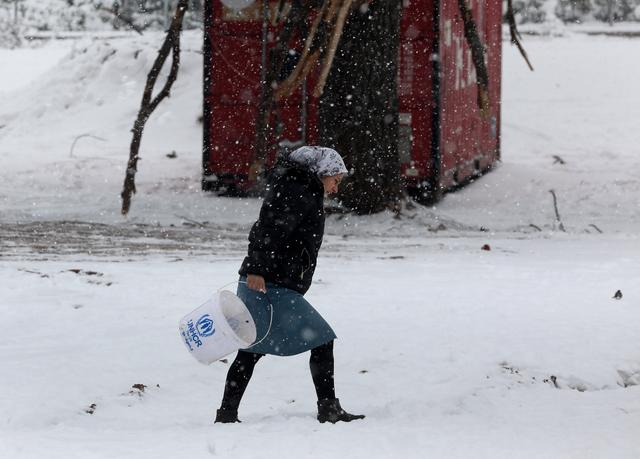 A stranded Syrian refugee braves a snowstorm at a refugee camp north of Athens, Greece January 10, 2017.REUTERS/Yannis Behrakis