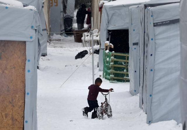 A stranded Syrian refugee child tries to move his bicycle during a snowstorm at a refugee camp north of Athens, Greece January 10, 2017.REUTERS/Yannis Behrakis