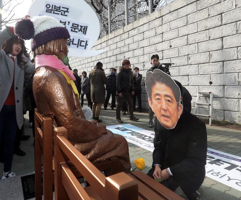 A man wearing a mask of Japanese Prime Minister Shinzo Abe kneels down in front of a statue of a girl that represents the sexual victims by the Japanese military during a rally in front of Japanese Consulate in Busan, South Korea, January 4, 2017.    Kim Sun-ho/Yonhap via REUTERS