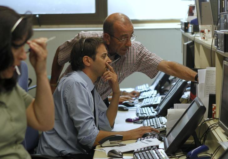 FILE PHOTO: Traders look at computer screens during Spain's bonds auction in a broker's office in Barcelona June 21, 2012. REUTERS/Albert Gea/Files