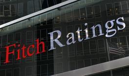 """En la imagen de archivo, una bandera de Estados Unidos reflejada contra el logo de Fitch Ratings en su sede de Nueva York. Los planes de reducir impuestos del presidente electo de Estados Unidos, Donald Trump, podrían poner en riesgo la nota de crédito """"AAA"""" del país en el mediano plazo, dijo el jueves Ed Parker, analista de calificación de deuda de la agencia Fitch.REUTERS/Brendan McDermid"""