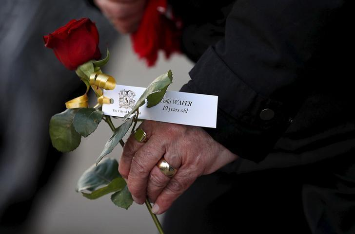 A family member carries a rose with a victim's name attached following a vigil in memory of the victims of the Hillsborough disaster in Liverpool, northern England April 27, 2016.REUTERS/Phil Noble/Files