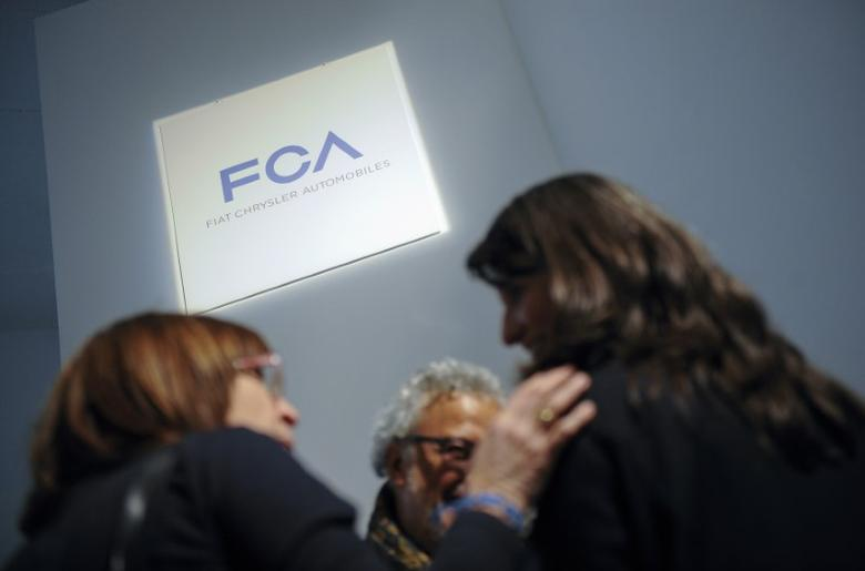 People talk as they stand next to a logo of Fiat Chrysler Automobiles (FCA) in Turin March 31, 2014. REUTERS/Giorgio Perottino